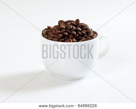 Coffee beans in a cup on a white background.
