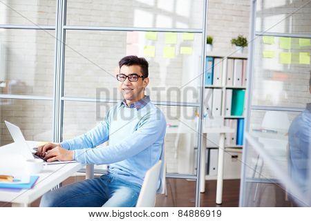Cheerful businessman in casualwear sitting by desk in office