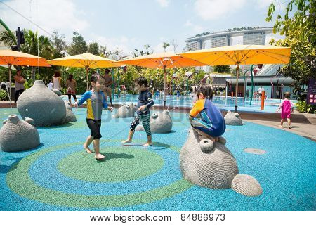 SINGAPORE - JANUARY 27, 2015: Happy children playing on the playground with water attractions in the popular park Gardens by the Bay. Park was opened in 2012 and is a striking sight of Singapore.