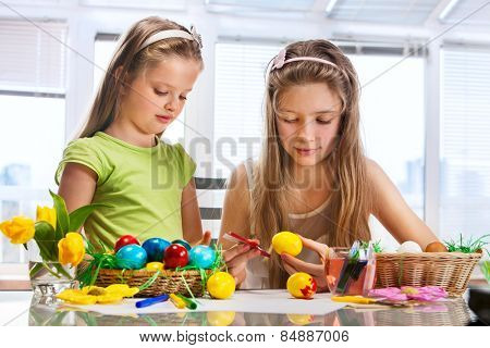 Children girl paint Easter eggs at home. Flowers in basket.