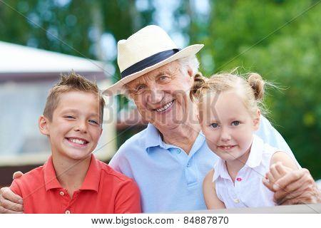 Portrait of a happy senior man with grandchildren