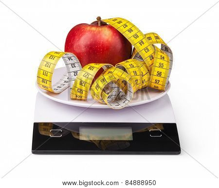 Apple with measuring tape on a digital kitchen scale