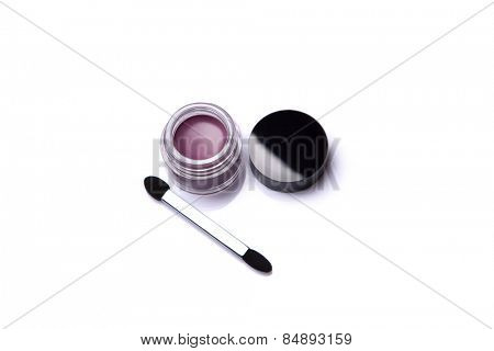 Pink lip gloss in jar with brush, isolated on white background with natural reflection