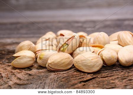 Roasted pistachios on wooden background