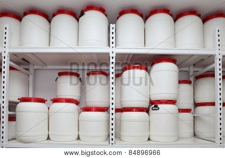 white chemical plastic barrels on shelves in storehouse