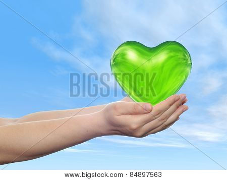 Conceptual 3D green abstract heart sign or symbol held in hands by woman or child over nice blue cloud sky background, metaphor to love, holiday, wedding, care, valentine, protection romantic