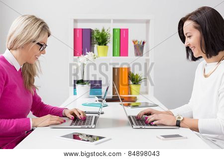 Two cheerful woman working with computers in the office