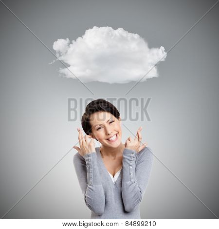 Young woman shows crossed fingers, isolated on grey background with cloud