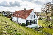 picture of dike  - Whitewashed house with shutters and orange tiles at the bottom of a Dutch dike on a cloudy day at the end of the winter season - JPG