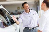 foto of showrooms  - friendly salesman selling car to a customer in showroom - JPG