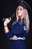 picture of cap gun  - Beautiful young woman in a marine uniform with a gun over black background - JPG