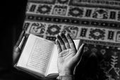 stock photo of quran  - Muslim Man Is Reading The Holy Quran - JPG