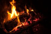 picture of ember  - Hot red embers from logs burning in fireplace - JPG