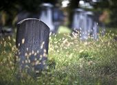 pic of burial  - Tombstone and graves in an ancient church graveyard - JPG