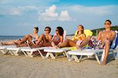 picture of sunbather  - Group of multi ethnic friends sunbathing on a deck chairs on a beach  - JPG