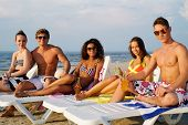 picture of sunbathers  - Group of multi ethnic friends sunbathing on a deck chairs on a beach  - JPG
