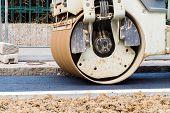 image of wheel loader  - Close up detail of the front wheel of a steamroller while working on asphalt lane - JPG