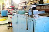 stock photo of workbench  - The image of a old vice on a metal workbench - JPG