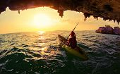picture of cave woman  - Young lady paddling the kayak from limestone cave towards open sea - JPG