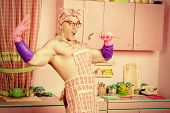 image of ladle  - Attractive muscular man in an apron posing with a ladle with expression - JPG