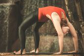 stock photo of dhanurasana  - Woman practicing yoga near waterfall - JPG