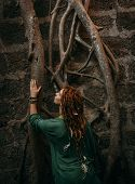foto of dreadlocks  - Rear View of Stylish Young Woman in Green Shirt with Dreadlocks Touching Tree Roots on the Wall - JPG