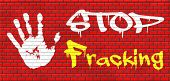 stock photo of ban  - stop fracking ban shale gas and hydraulic or hydrofracking graffiti on red brick wall - JPG