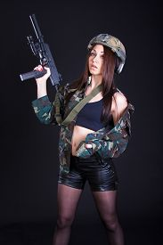 image of sub-machine-gun  - Beautiful young woman in a military uniform with a submachine gun over black background - JPG