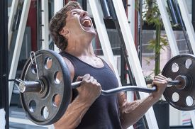 picture of struggle  - Muscular Caucasian man in tank top painfully struggles to complete repetition of arm curls in gym - JPG