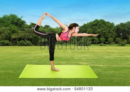 Young Woman Doing Yoga Exercise With Yoga Mat On Green Grass