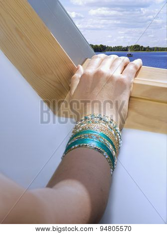 Woman's Hand With Bracelets On  Edge Of A Skylight's Frame