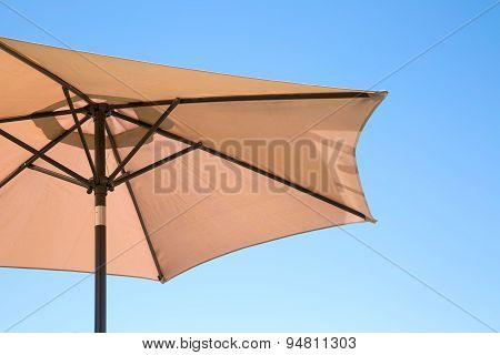 Beige parasol on a clear blue sky