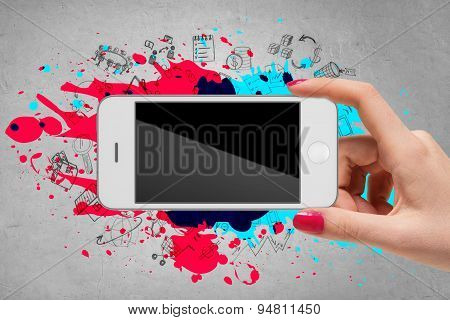 Woman hand holding mobile phone on grey background with splatters and doodles