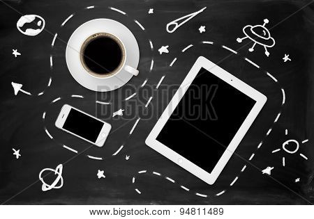 School blackboard with doodles, tablet, mobile phone and cup of coffee on it