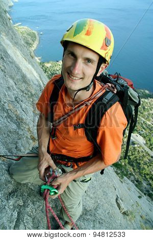 Young male climber hanging by a cliff on wide alley background