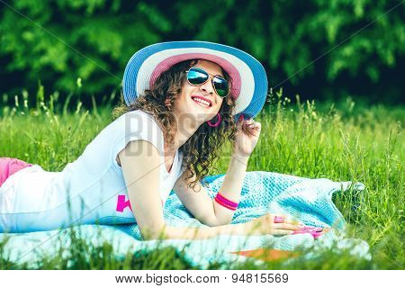 Pretty Girl Outdoor Lying On The Grass In The Park