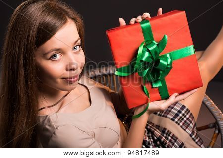 Sensual  attractive girl sits on a chair with gift in her hands