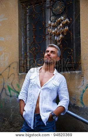Sexi Man In A White Shirt And Ornamental Window On Background. And Dream Catcher.