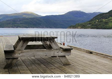 Wooden table on the lake shore