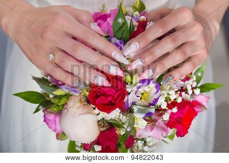 beautiful wedding bridal bouquet of roses and peony with her hands on the bouquet, long acrylic nail