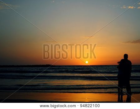 Young Couple Watching Sunset In Tel Aviv Beach