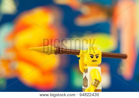 Sofia, Bulgaria - May 6, 2015: Single yellow plastic minifigure character holding spear
