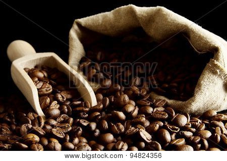 Overturned Bag Full Of Coffee Beans On Black With Spatula