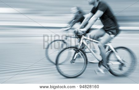 Young Man And Woman Riding Bicycles On A City Street