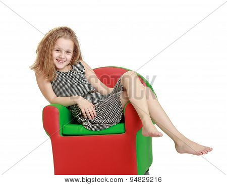 Cute cheerful teenage girl lay colored leather chair