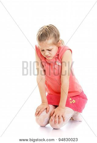 Sad, offended little girl sitting on the floor with bent down he