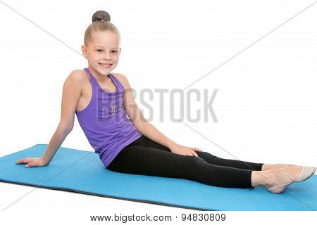 Slender beautiful young girl who is engaged in fitness sitting o