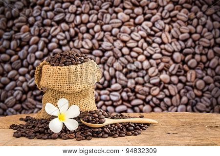 Coffee Beans In Burlap Sack On Wooden Table With Blurred Background