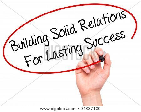 Man Hand writing Building Solid Relations For Lasting Success with black marker on visual screen.