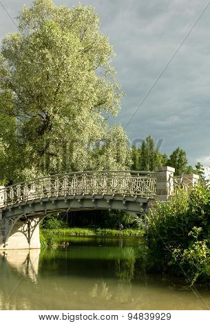Beautiful delicate bridge across the river in the park